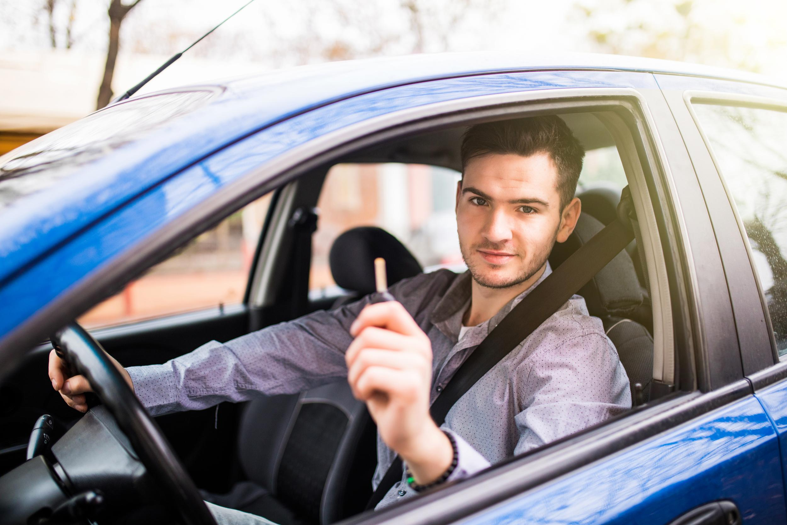 young-handsome-man-driving-his-new-car-holding-out-keys.jpg