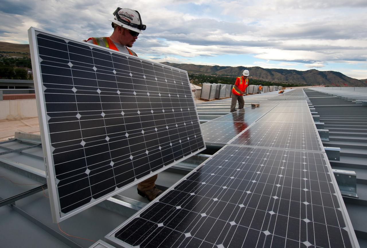 Solar Industry At Work. Brian Lawson and Kenesaw Burwell work on panels that the Energy Department is using to leverage a Power Purchase Agreement with Sun Edison and Xcel Energy.