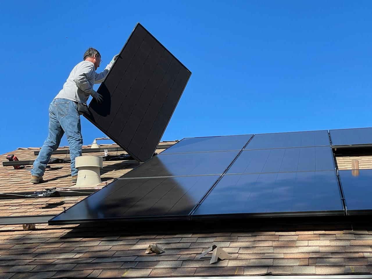 Image of a man on a roof performing solar system service maintenance.