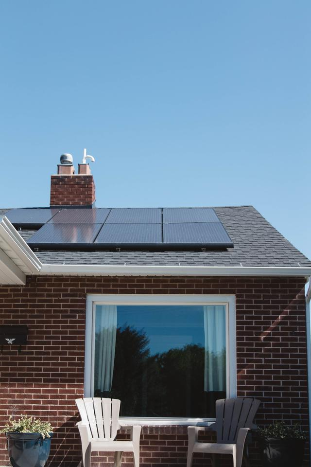 Vivint Solar - Solar Panels on roof of brick home with window and Adirondack chairs.