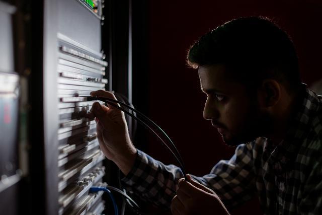 Male broadcast engineer works in studio