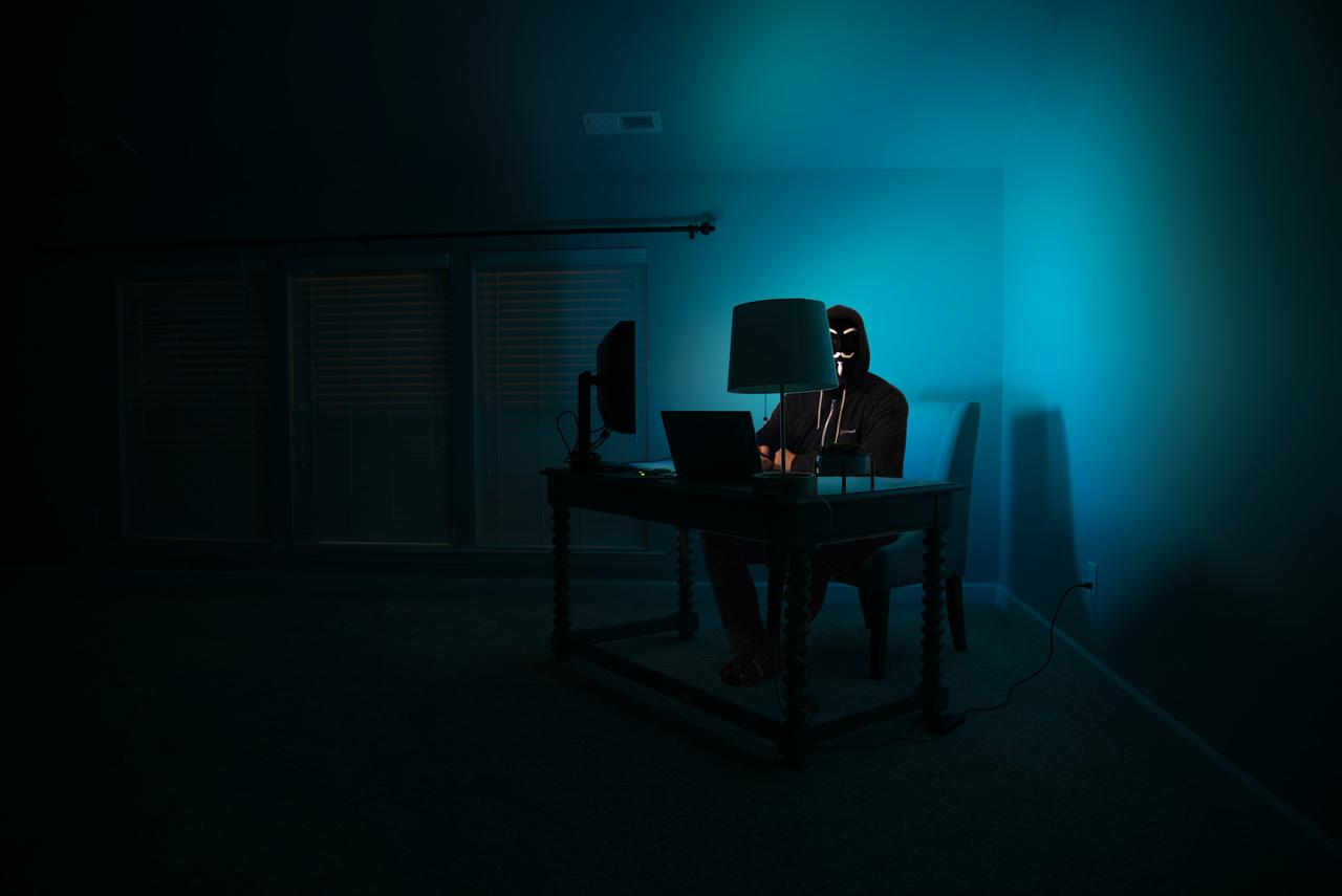 Pictured - a man at a computer disguised as an anonymous hacker wearing a Guy Fawkes mask.