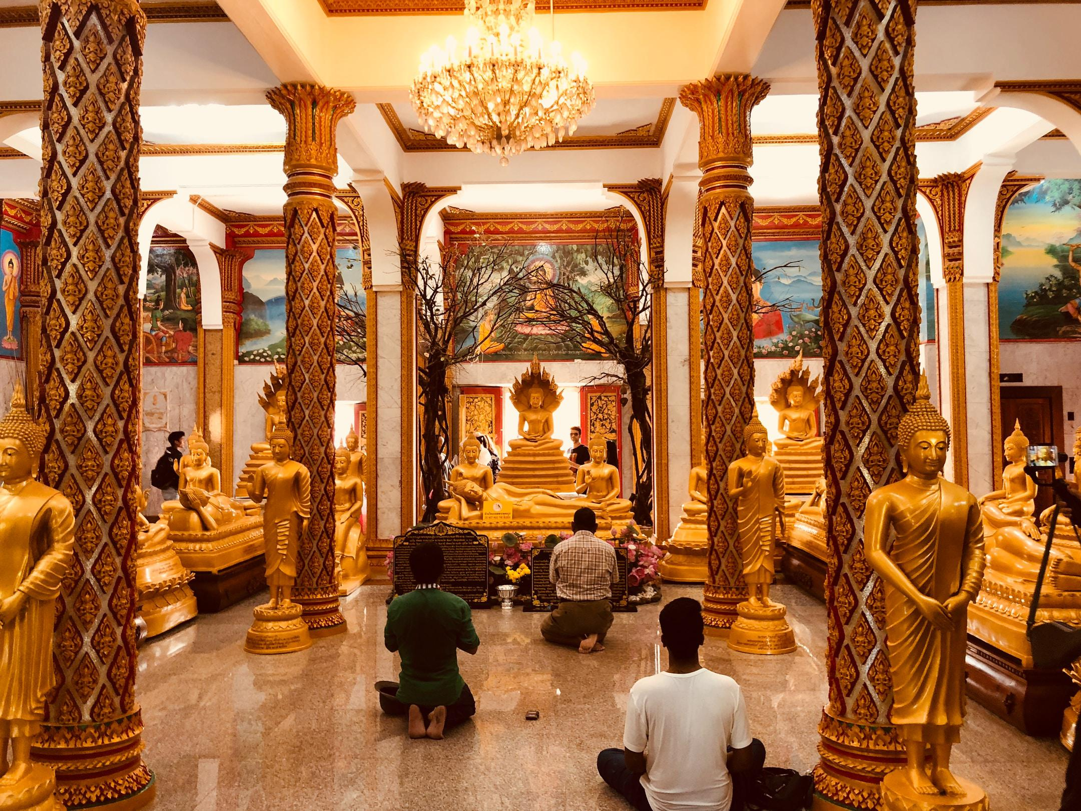 People praying inside Thai Buddhist temple with gold accent.