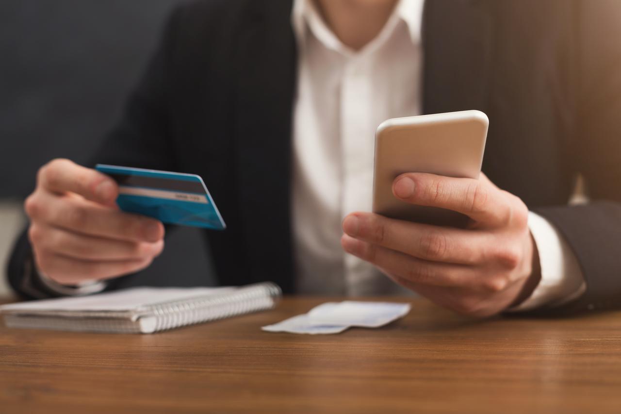 mans-hands-holding-a-credit-card-and-using-smartph-pkd6nug.jpg