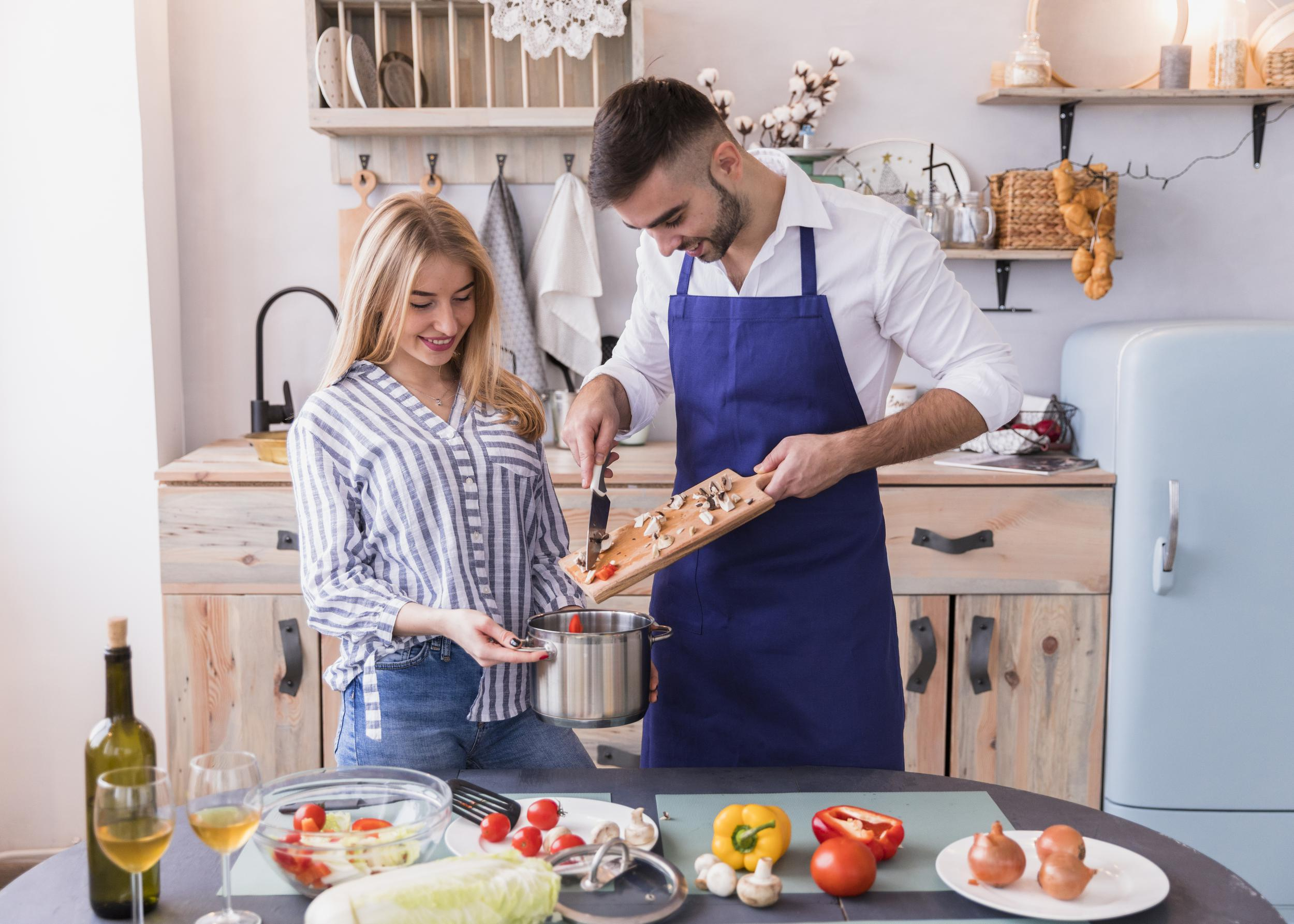 man-putting-vegetables-pot-in-kitchen.jpg