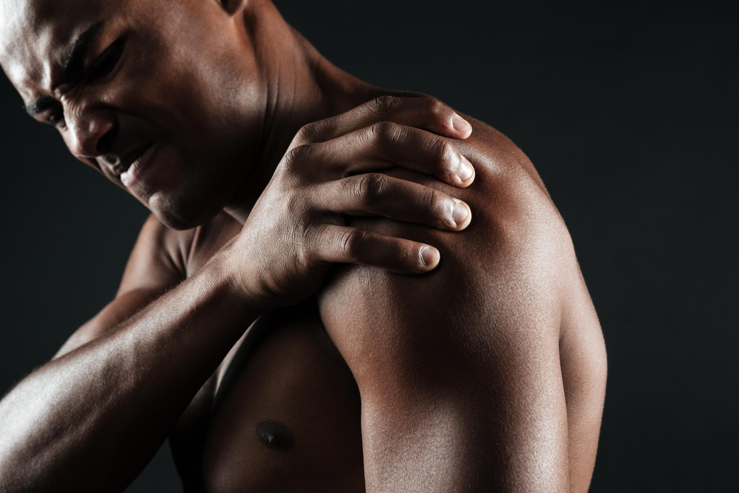 shirtless man holding his shoulder and wincing in pain