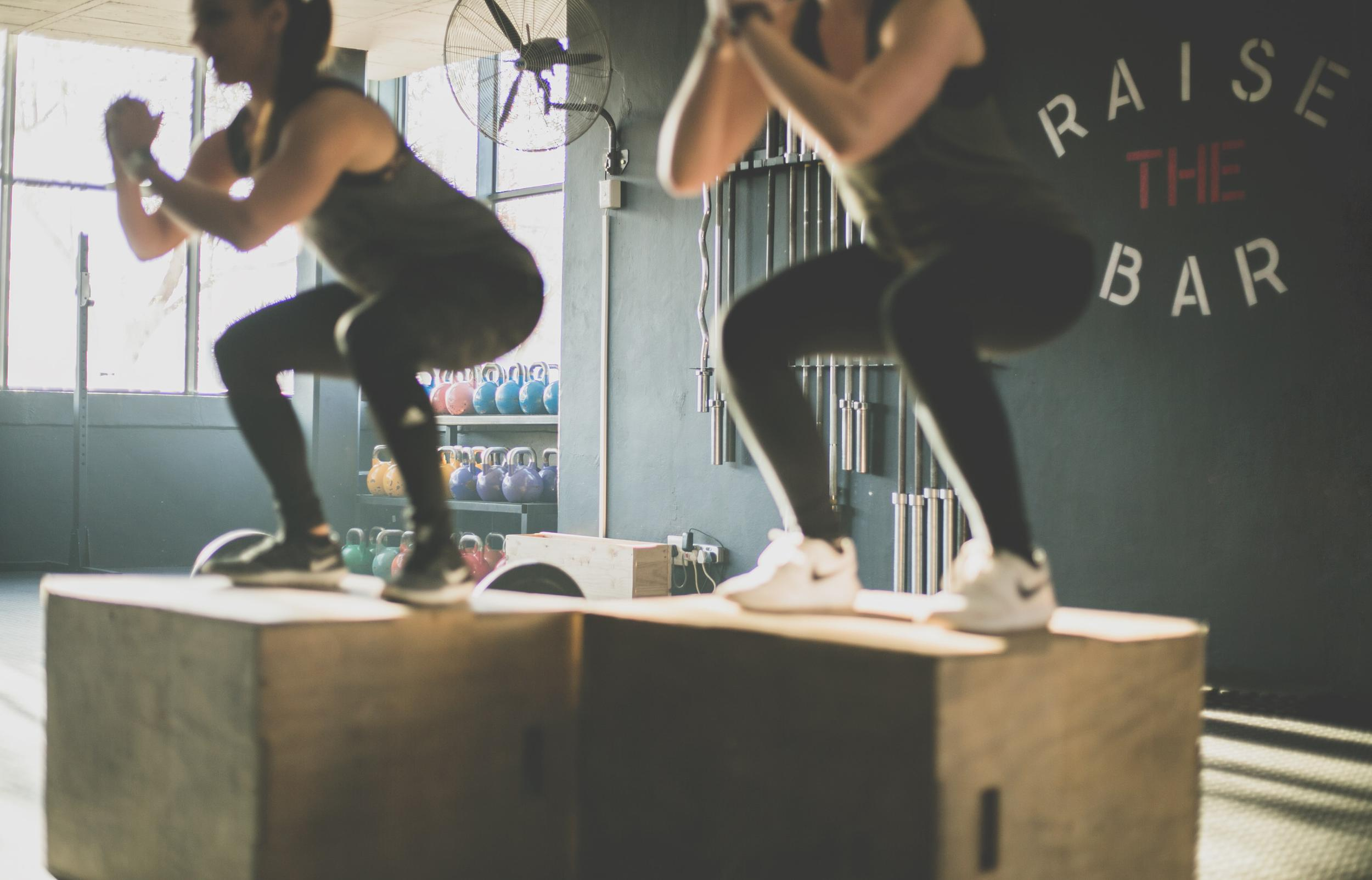 two women doing box jumps in a gym