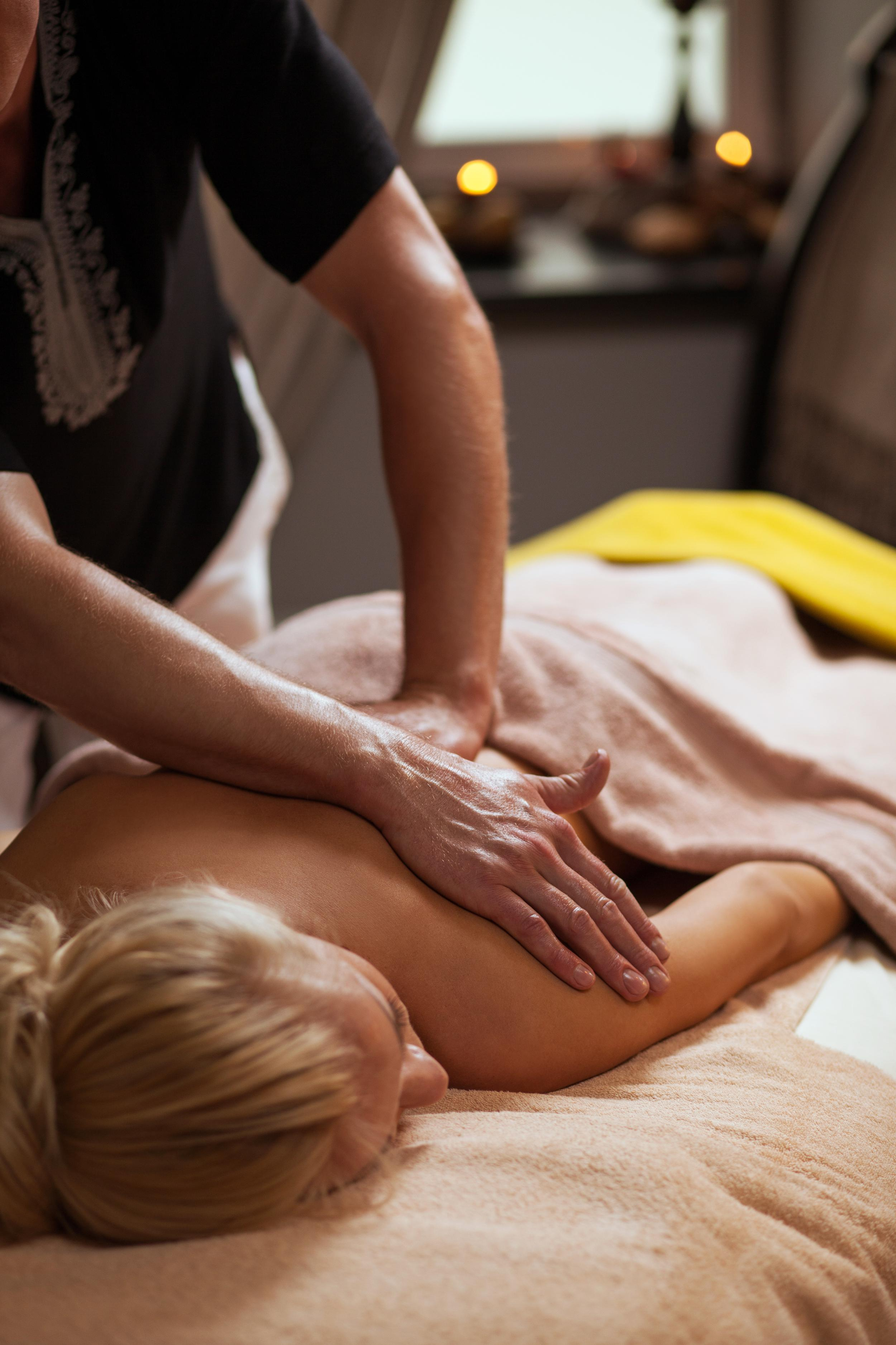 woman lying face down and getting a massage