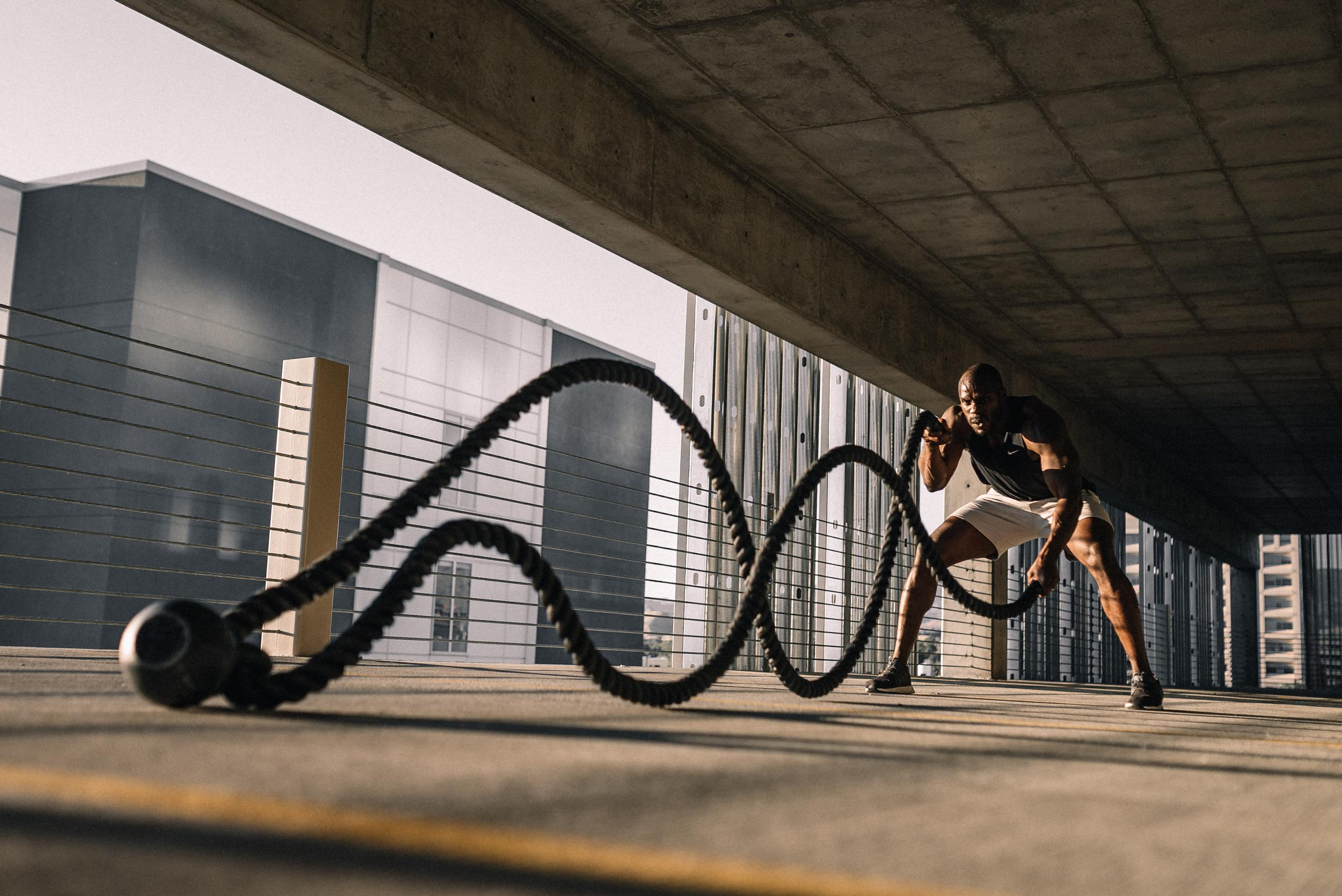 man using battle ropes in a parking structure