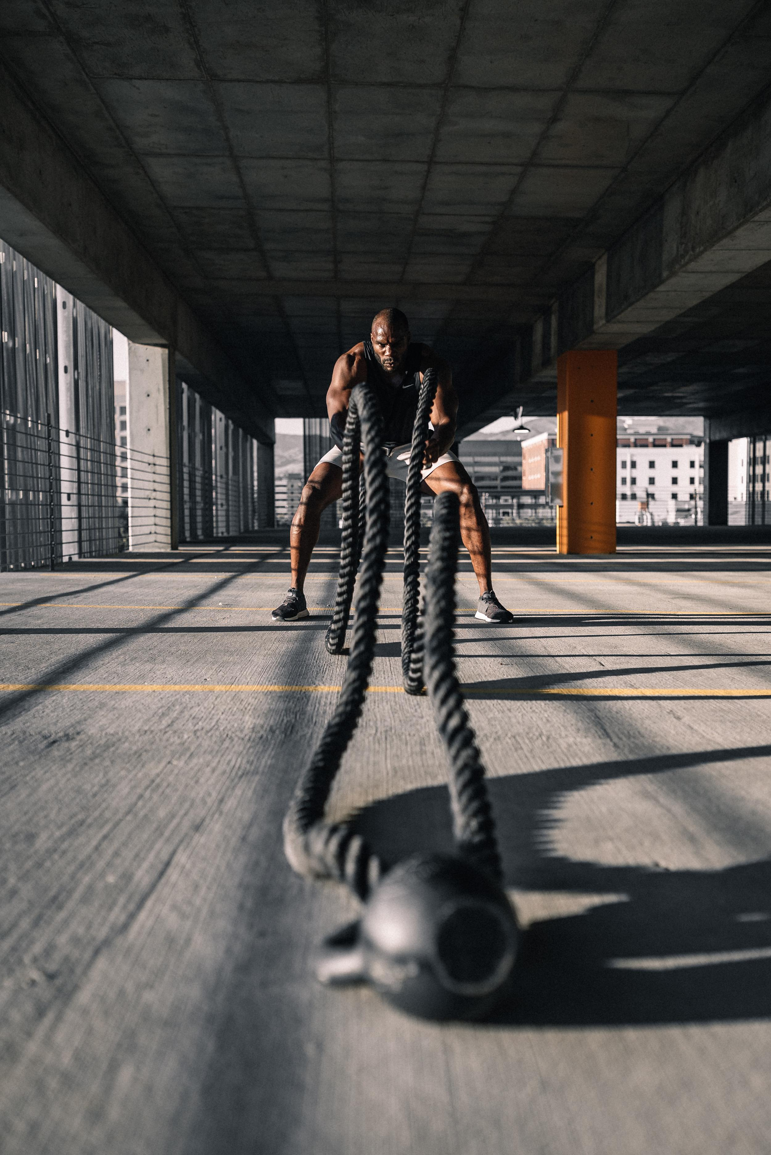 man working out with battle ropes in a parking structure