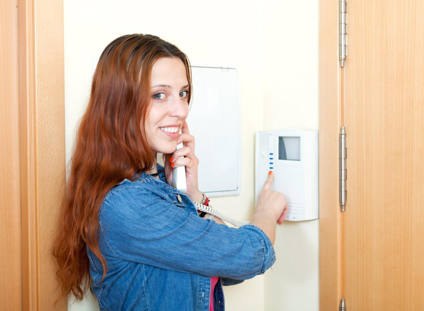 woman on phone using her home security alarm