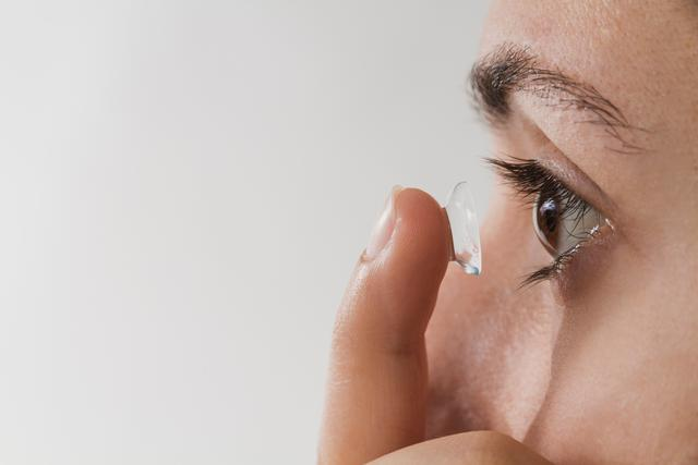 woman inserting a contact lens in her eye