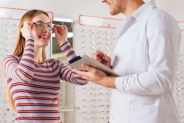 optometrist helping a patient try on glasses