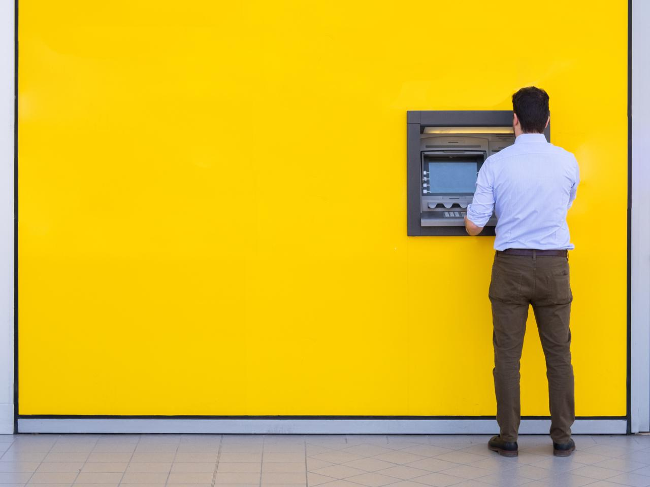 A man using an ATM that's installed in a yellow wall. One of the many reasons to purchase an ATM machine is walk-by traffic just like this!