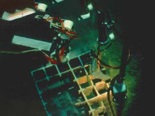 A machine underwater uncovering a grate.