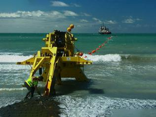 A yellow machine on the shoreline helping lay submarine cables.