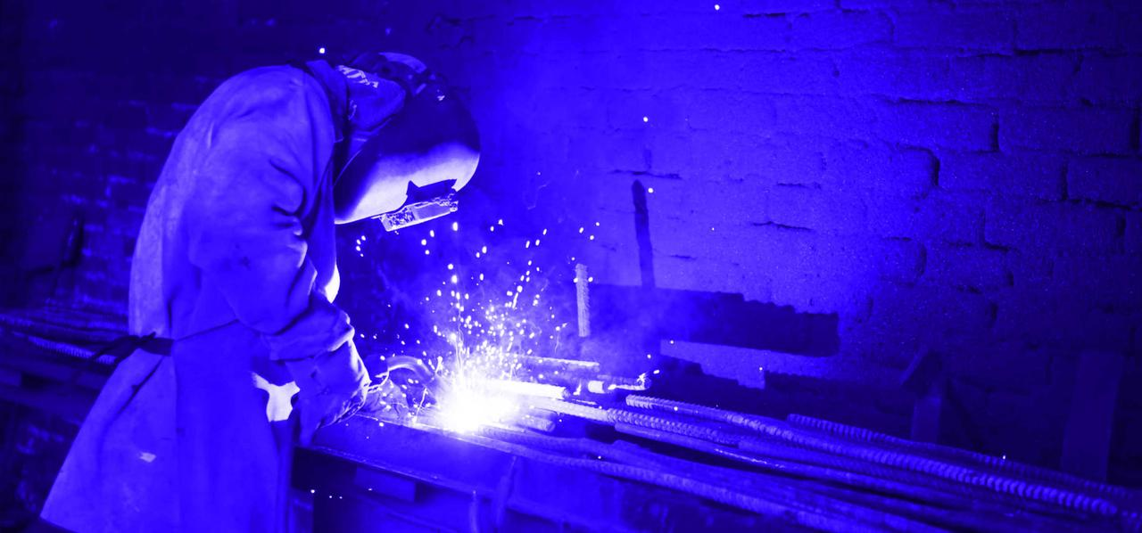 A person welding a piece of steal.