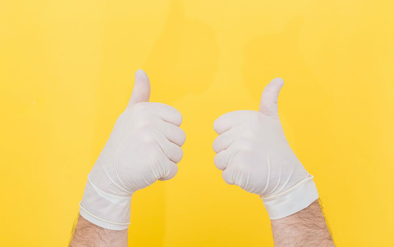 The close plan. Two hands in white medical gloves on a yellow background show thumbs up, like. The medicine. Place for an inscription. Advertising. All right. Like. Medical gloves.