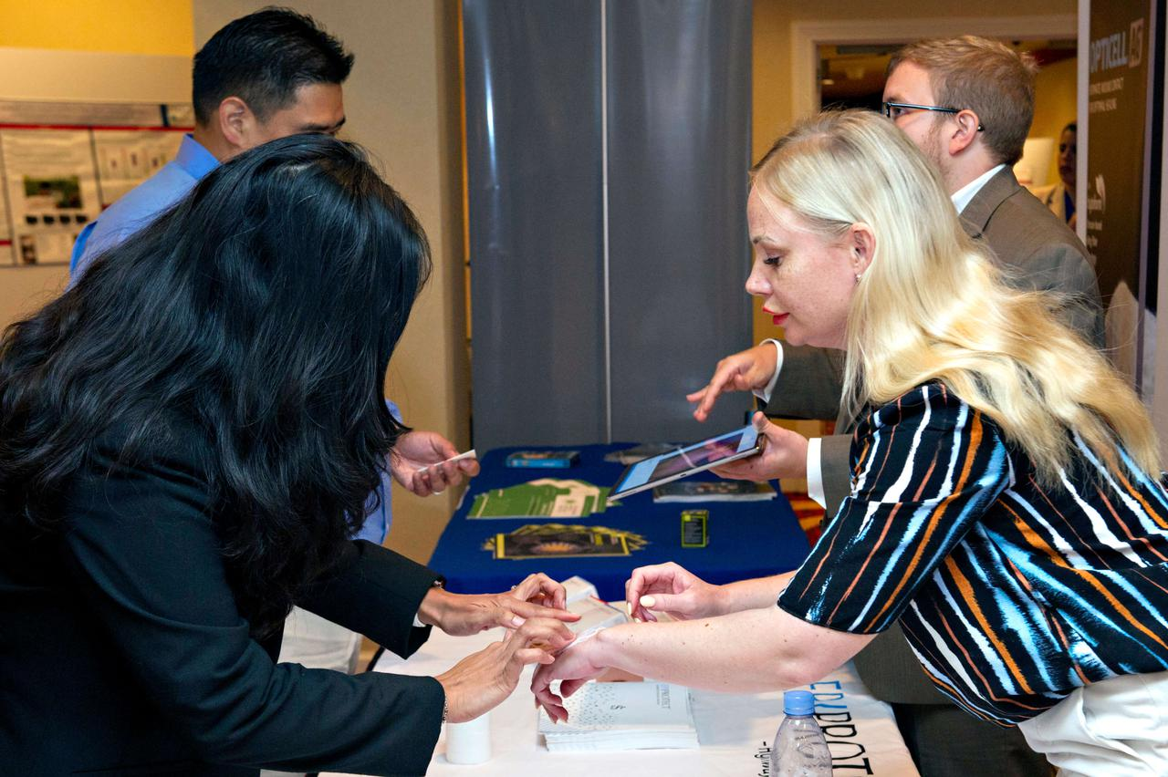 A woman having something applied to her hand at a booth during one of our wound care trade shows.