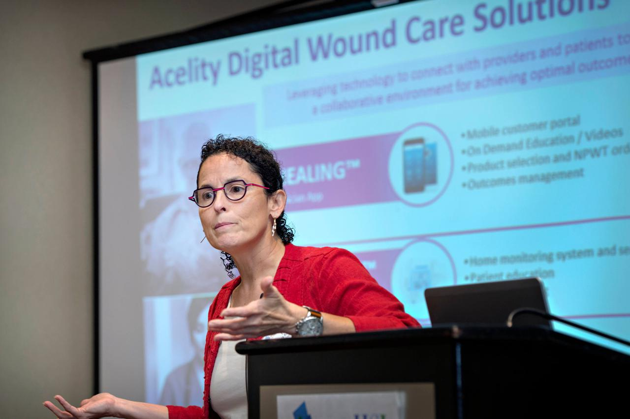 A woman standing beside a podium, presenting about acelity digital wound care solutions.