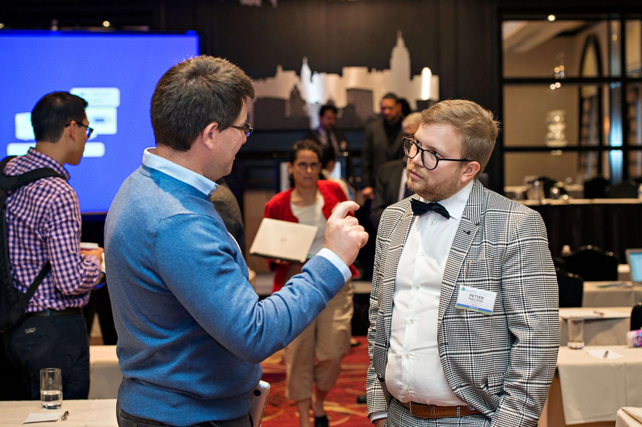 One man talking and gesticulating while another listens carefully.