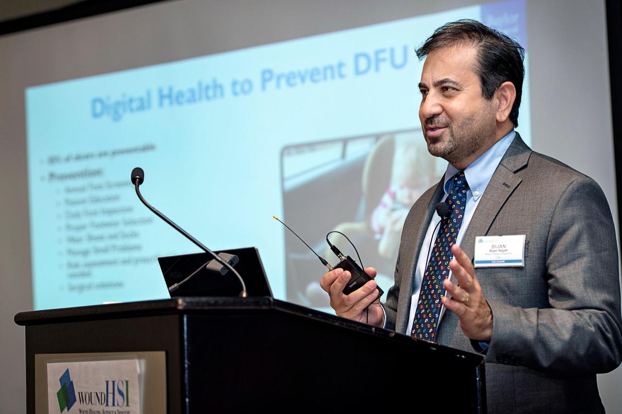 A speaker at a podium talking about digital health at one of our wound care trade shows.