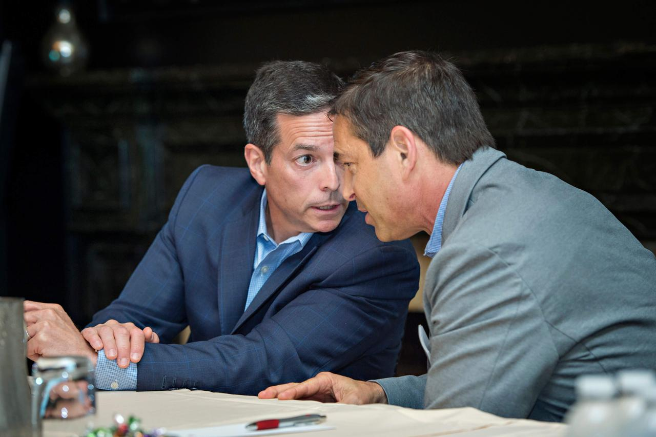 Two men quietly discussing wound healing and wound care during a presentation.