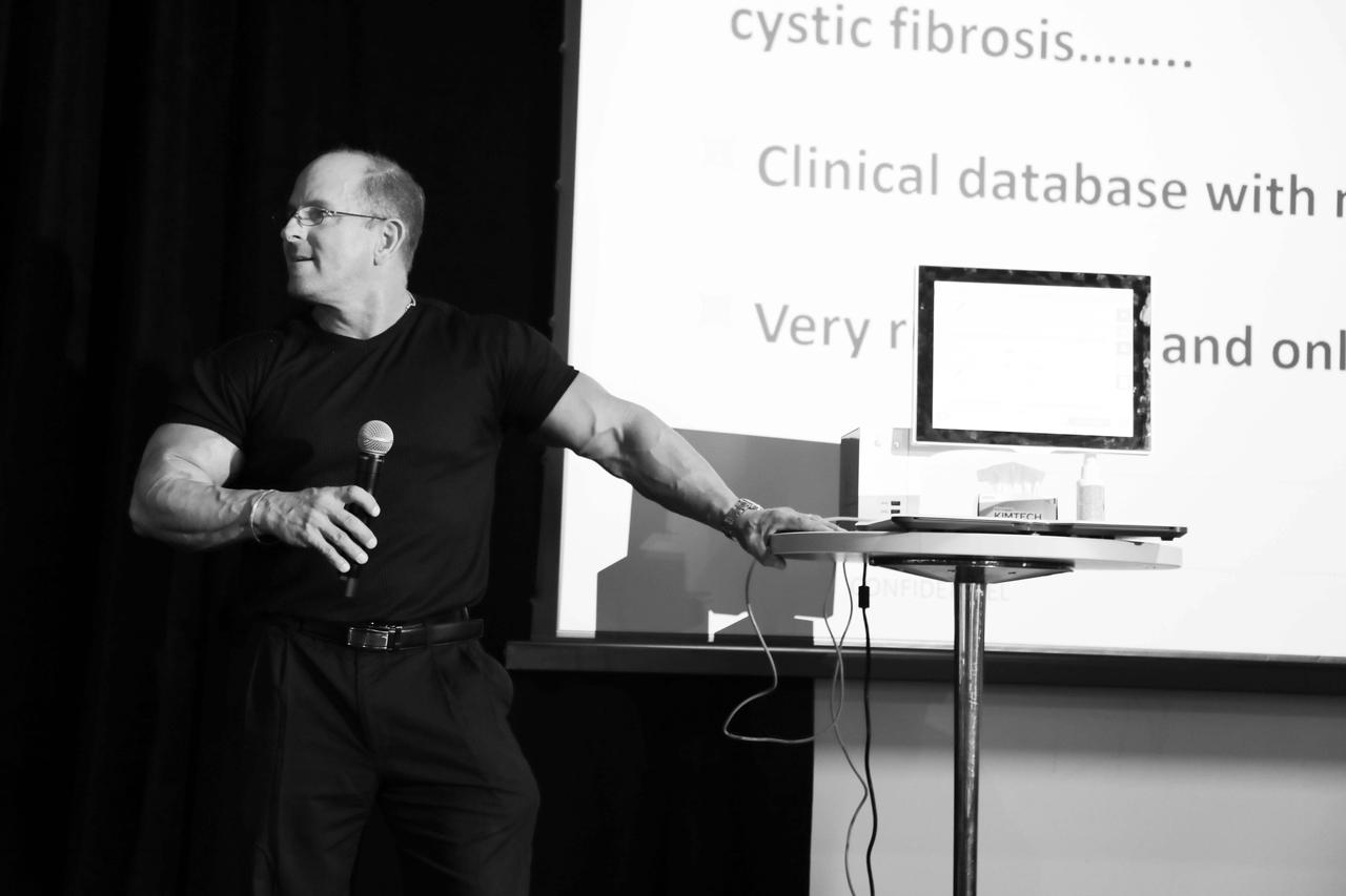 A man giving a presentation on cystic fibrosis, holding a microphone, and listening to someone offstage.