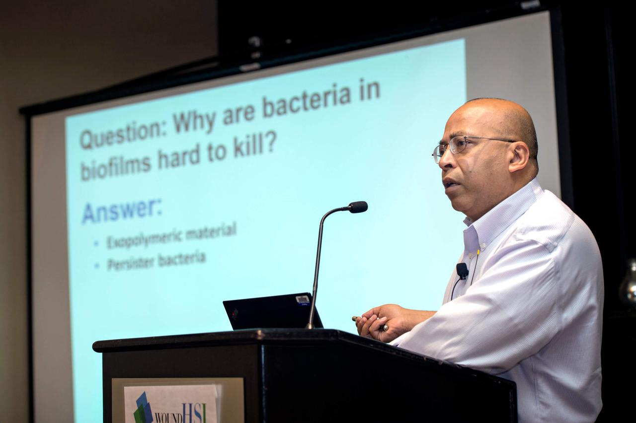 A man giving a presentation at a podium about bacteria in biofilms.