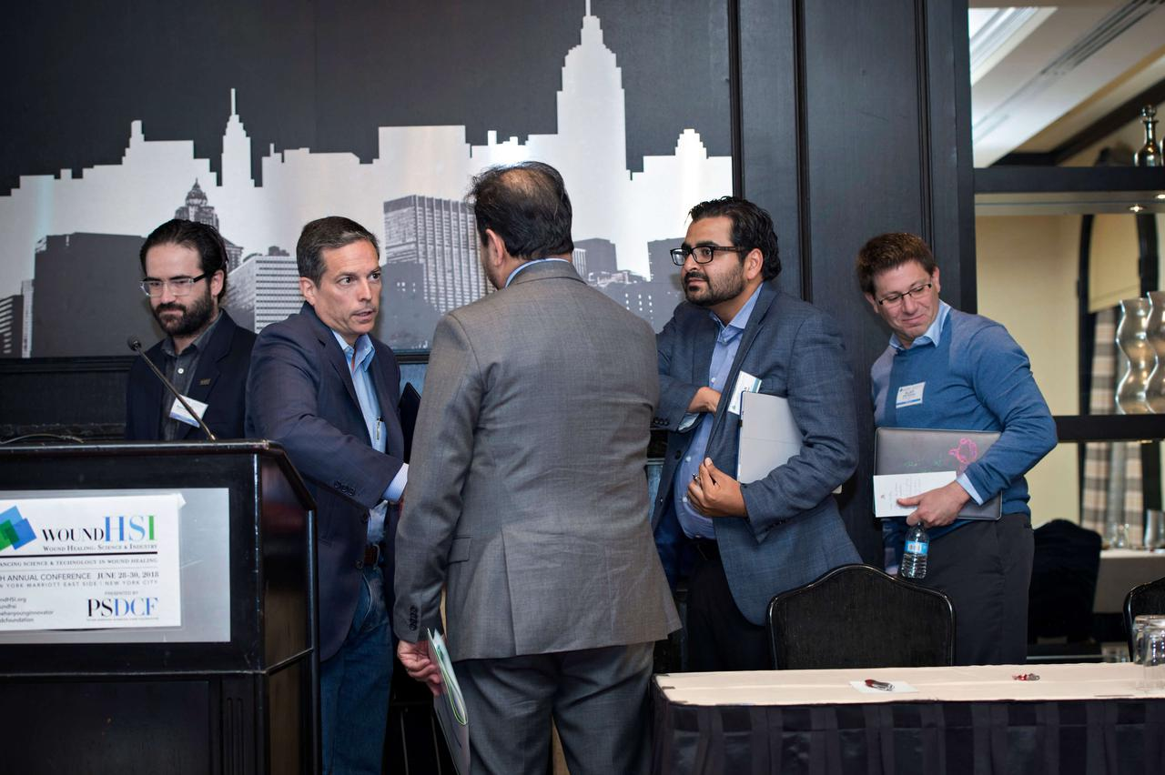 Panel members, speakers, and members of wound care organizations introducing themselves to each other before presentations commence.