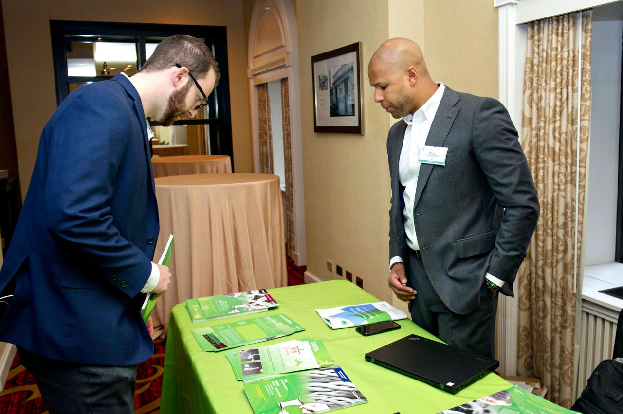A man reviewing pamphlets at a booth.
