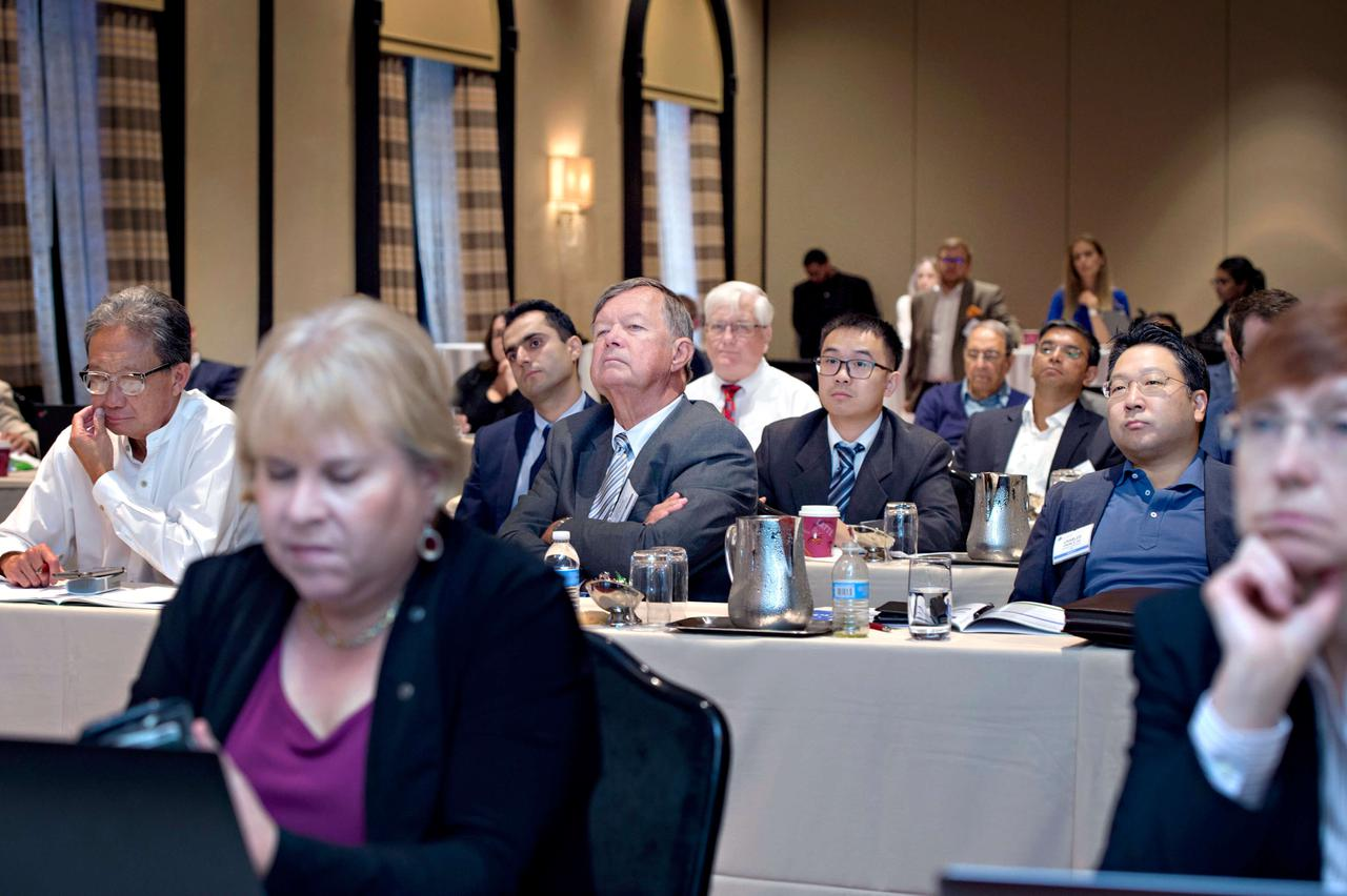 An audience paying close attention to a presentation during a wound care trade show.
