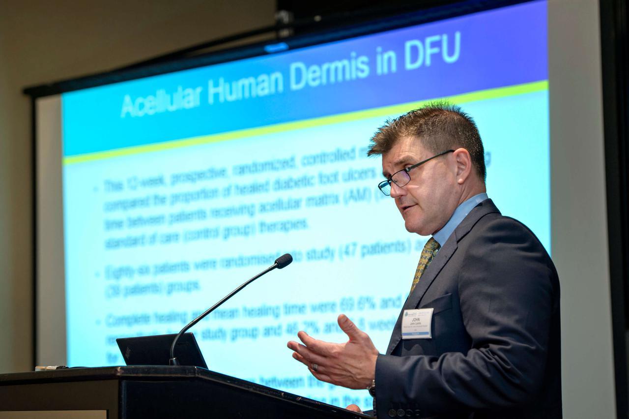 A man giving a presentation a podium about acellular human dermis.