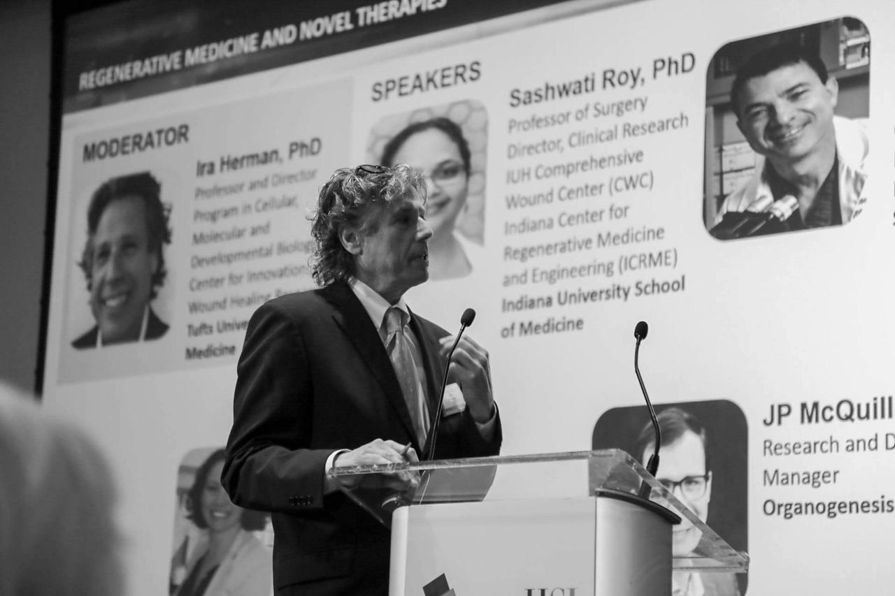 A man introducing the speakers and moderator at a wound care conference in 2021.
