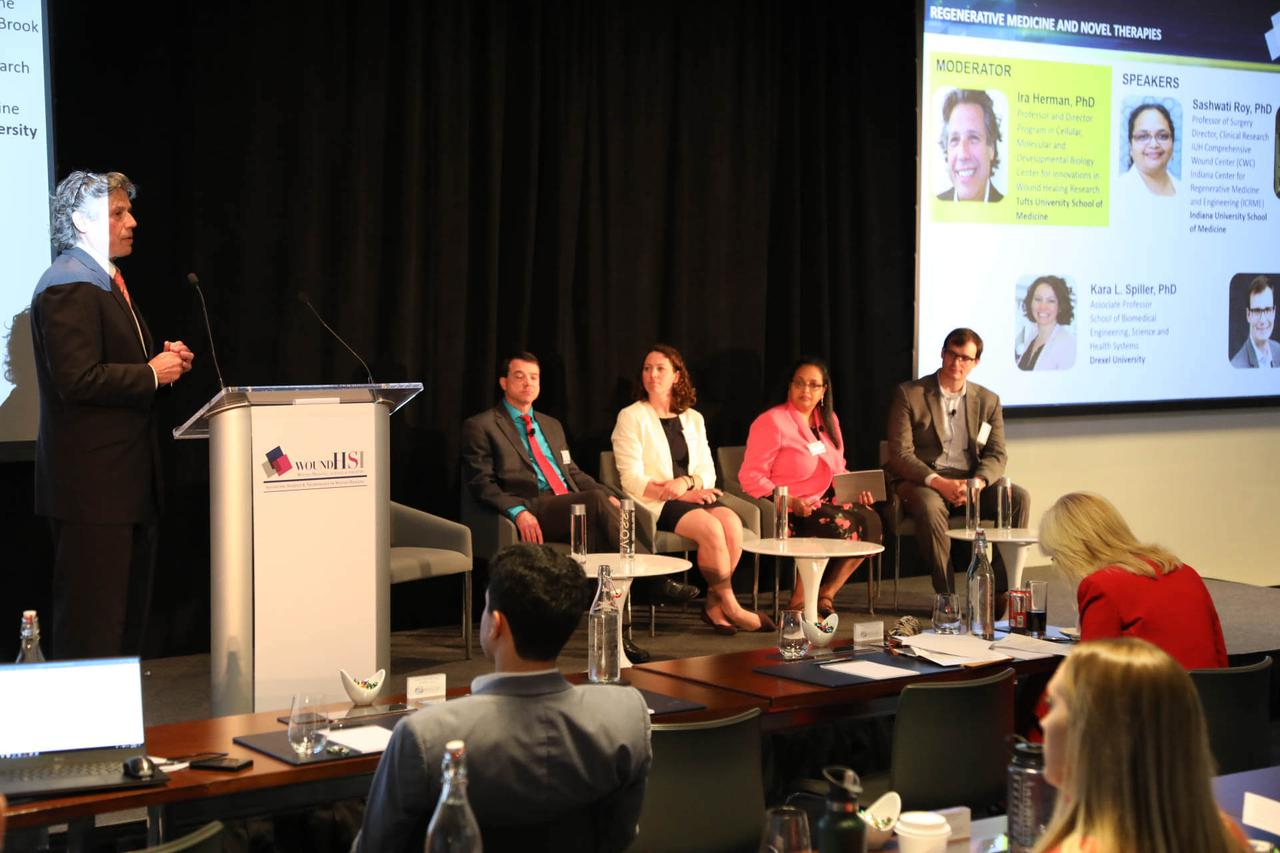 A man speaking at a podium while a panel of experts listen attentively.