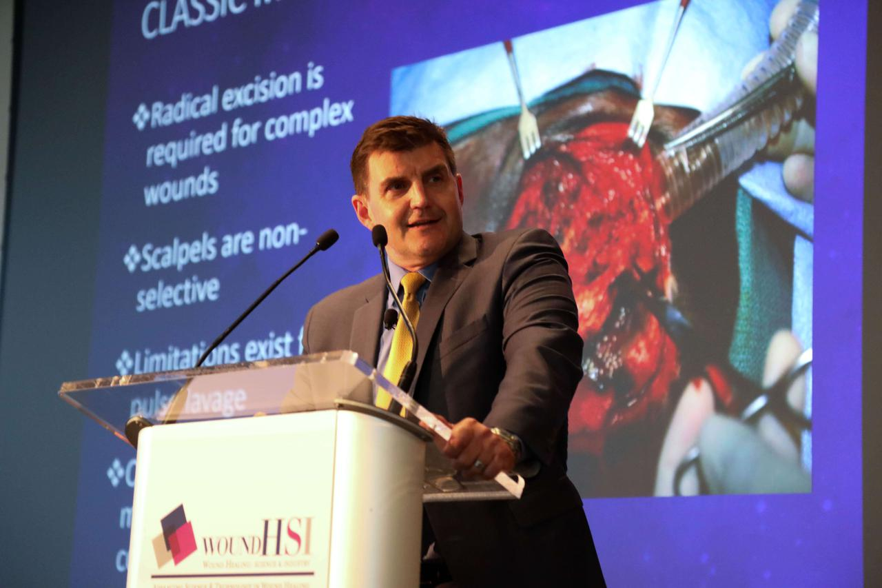 A man giving a presentation about surgery at at, and ultimately, providing advanced wound care education.