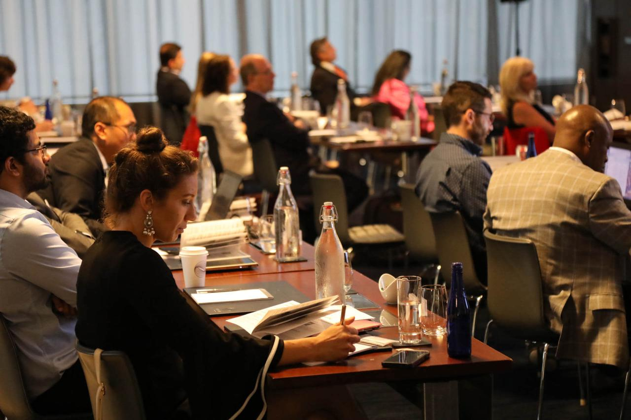 An audience taking notes and listening in rapt silence to a presentation.