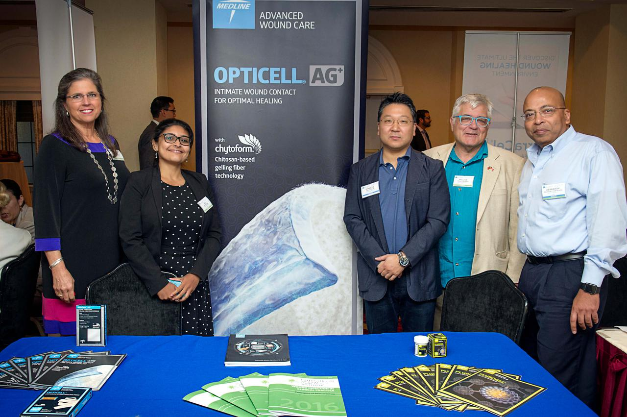 Several experts and members of wound care organizations proudly, and happily, standing behind their booth at a conference.