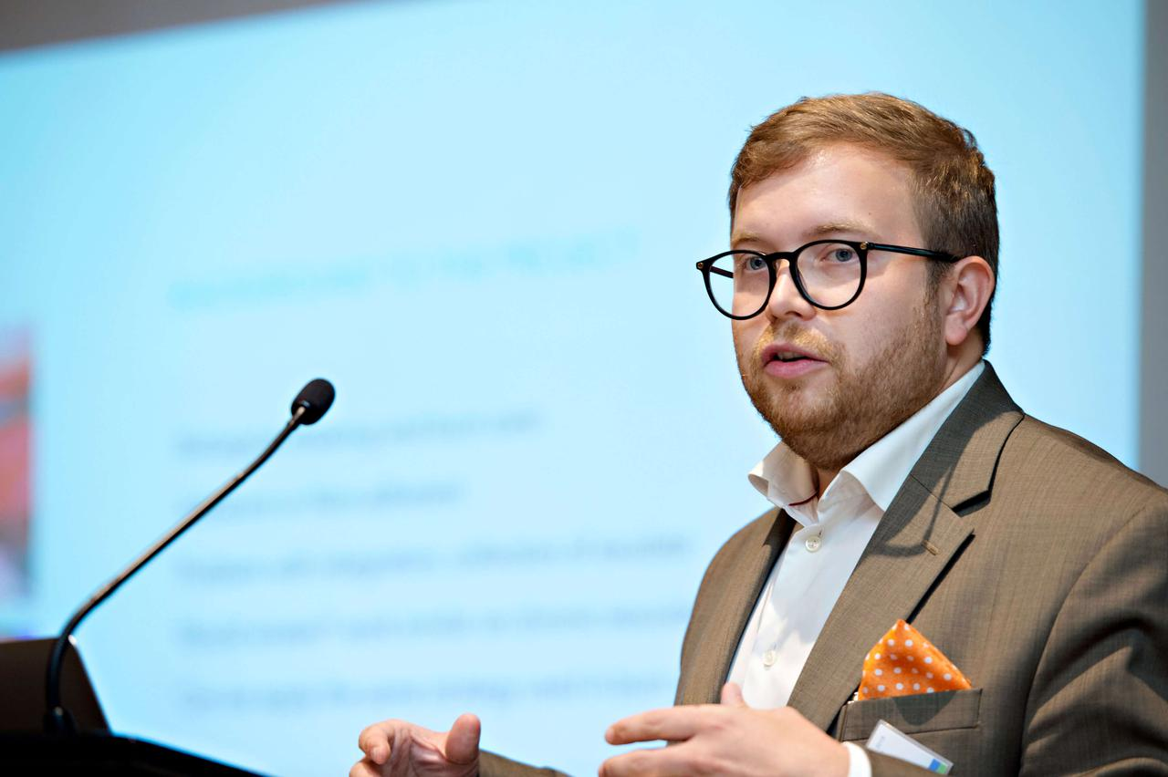 A man with a purple pocket square breaking down a problem at a podium.