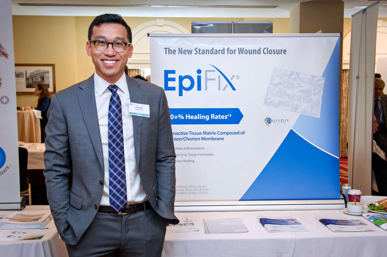 A man smiling in front of a booth and picture.