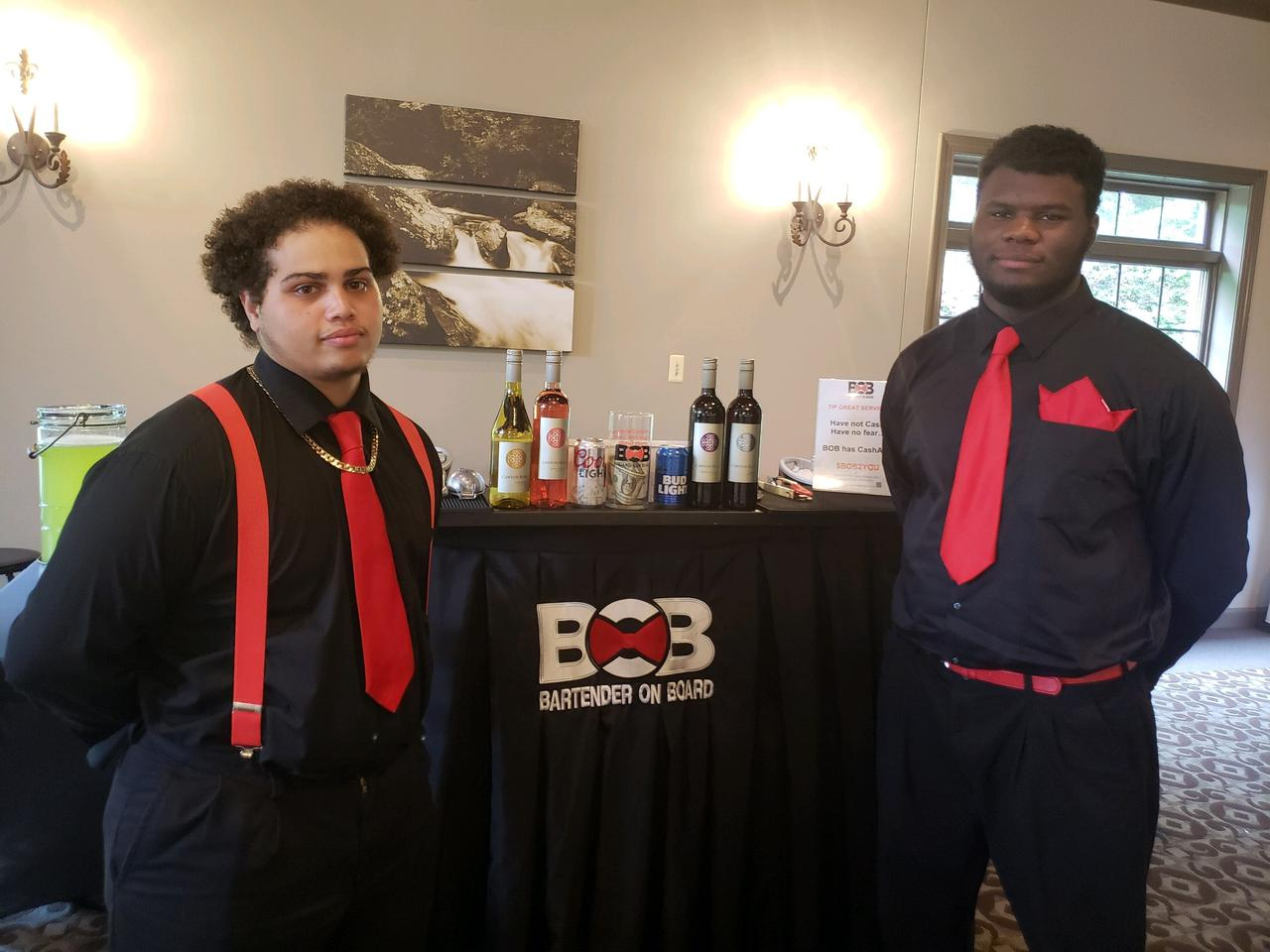 two bartenders posing in front of a mobile bar