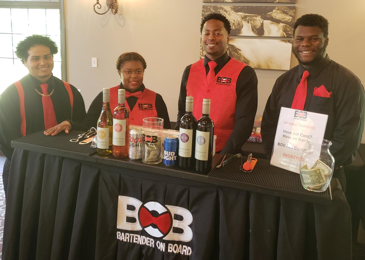 four bartenders standing behind mobile bar
