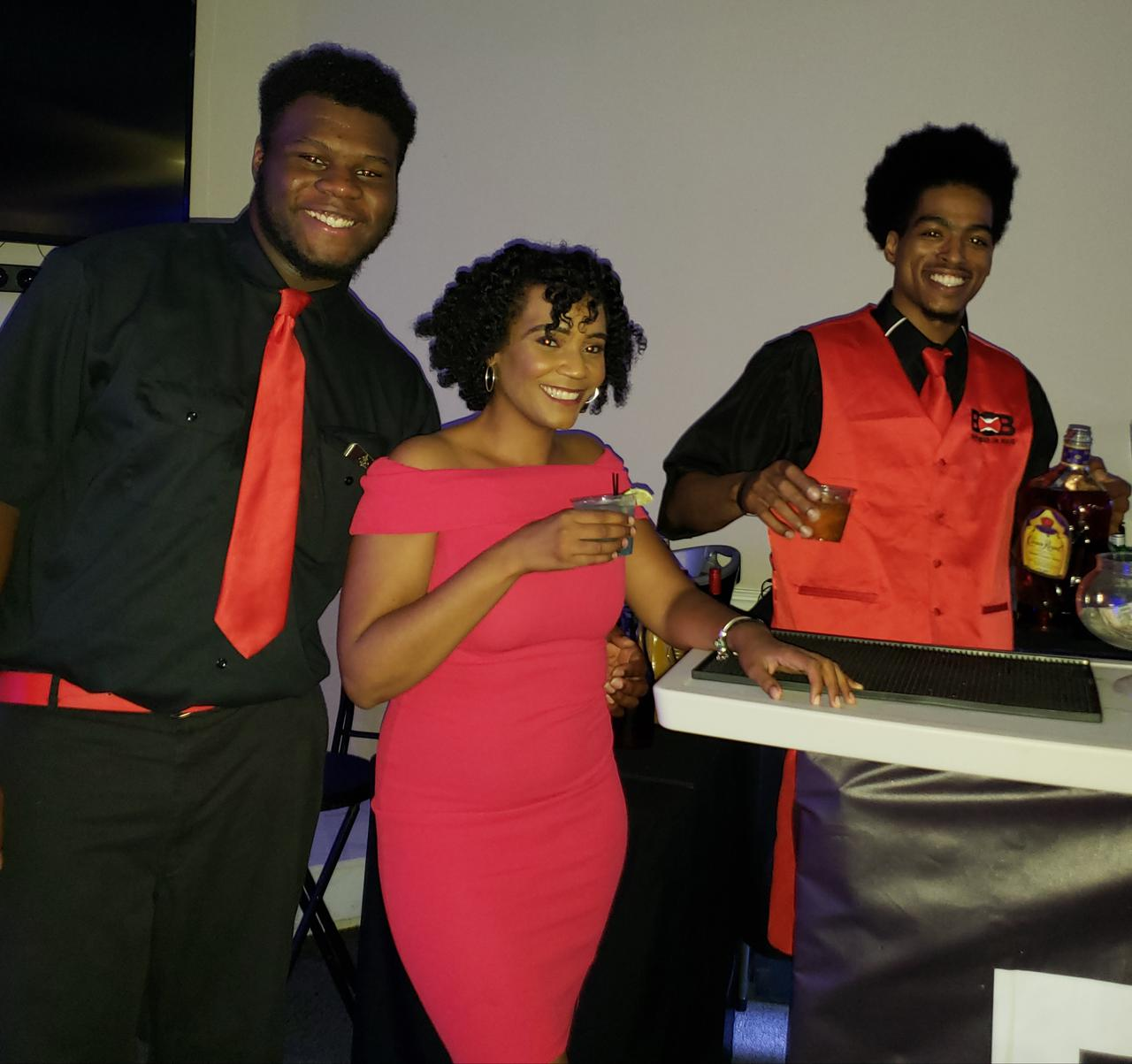 bartenders posing with event patron