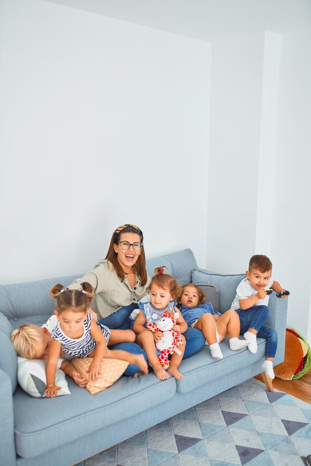 Beautiful teacher and group of toddlers sitting on the sofa playing at kindergarten