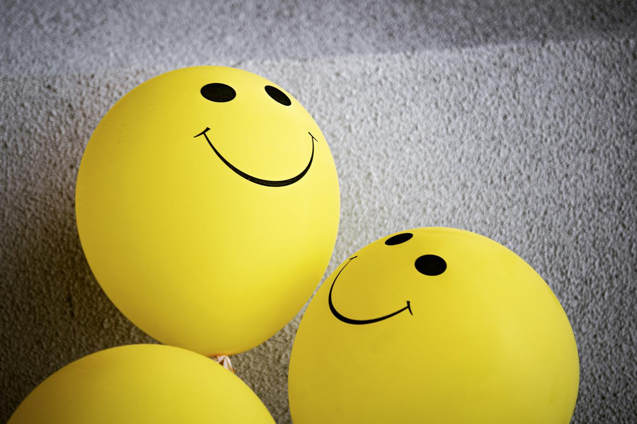 Bright yellow happy face balloons, showing smiling, friendly, welcoming admiration.