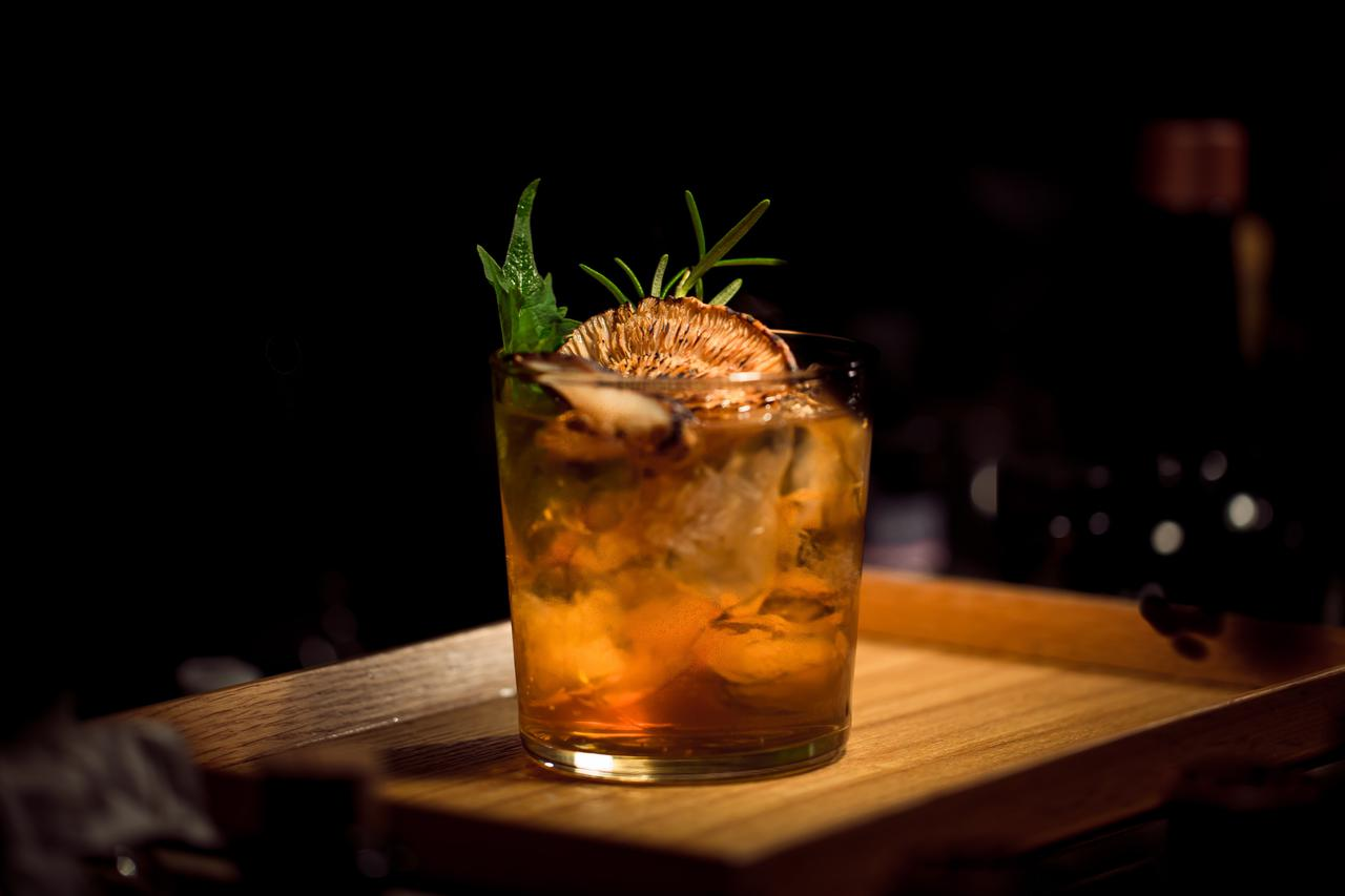 An exotic cocktail on a wood serving tray.