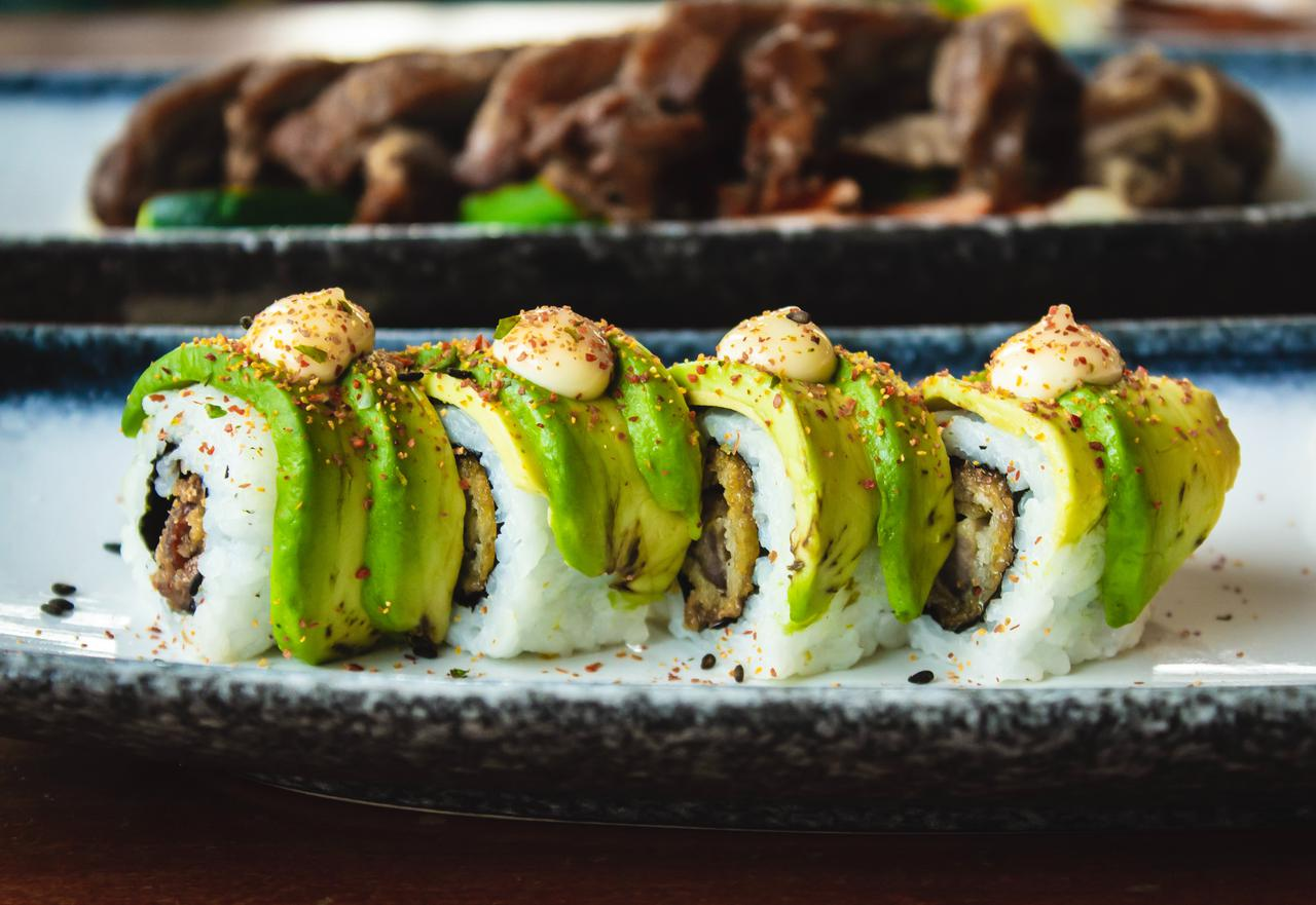 Sushi with avocado lined up and cooked meat in the background.