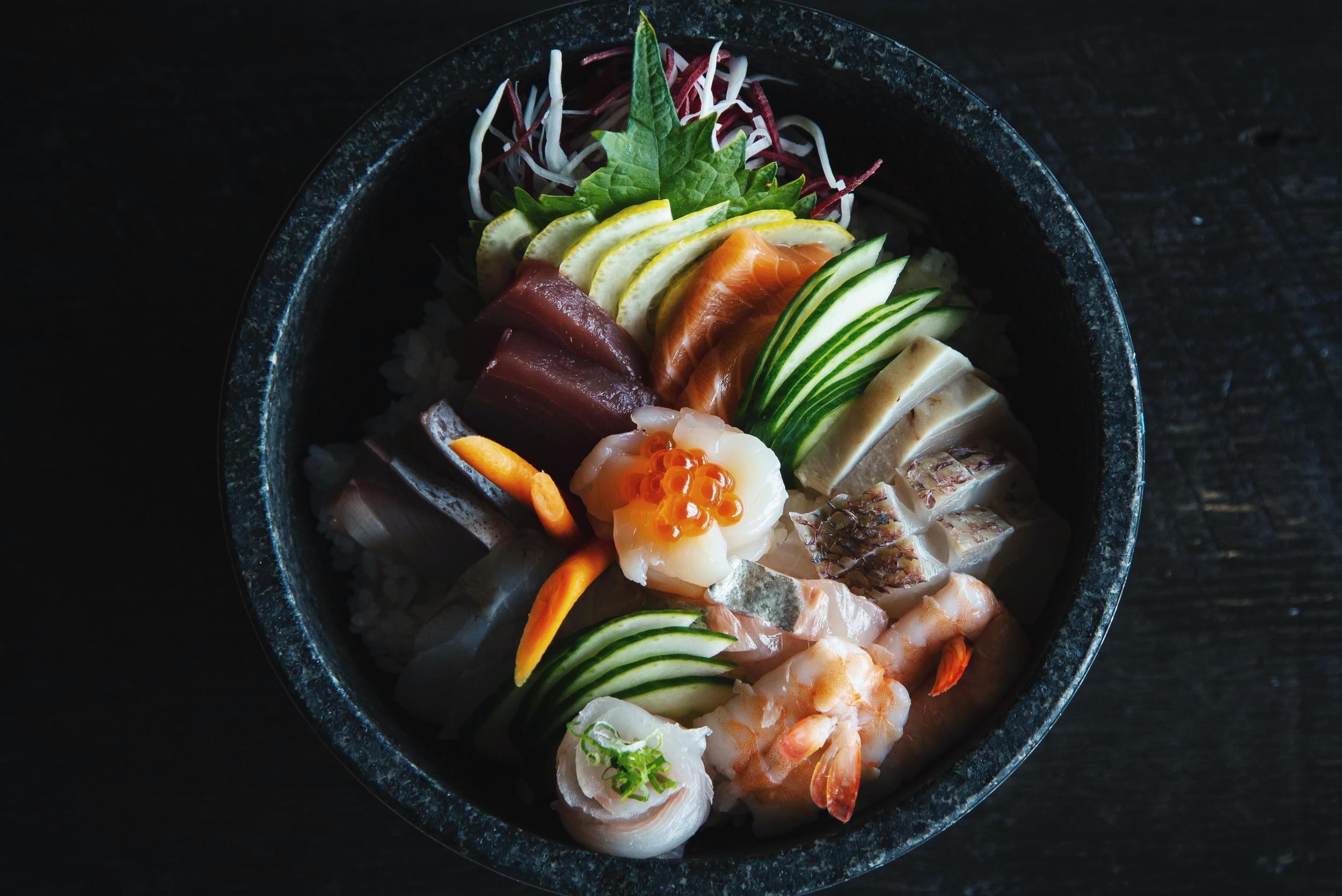 A plate of sushi and veggies arranged beautifully.