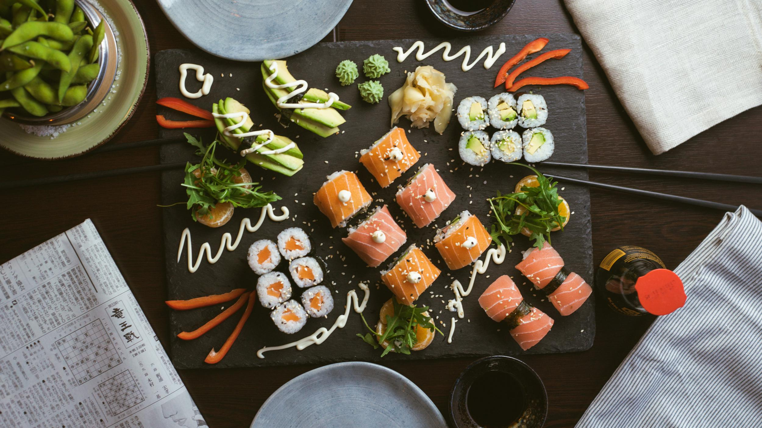 A platter of different kinds of sushi with sauce.