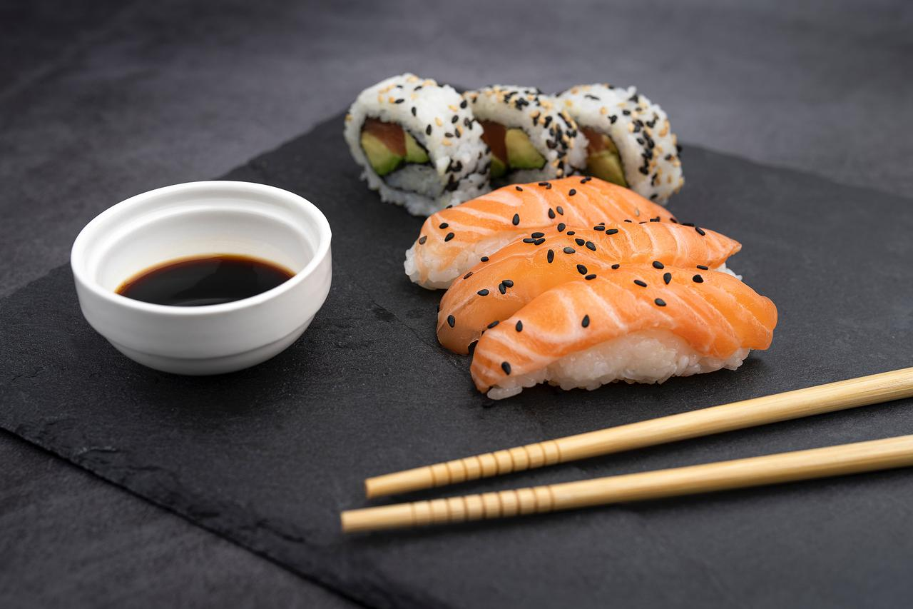 Two types of sushi, a dish of soy sauce, and chopsticks on a mat.